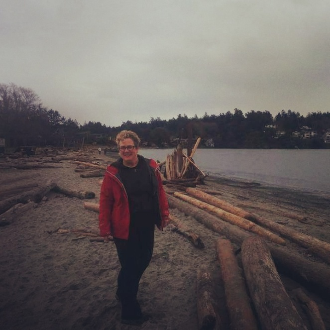 Image description: Sam in her red raincoat enjoying a grey day at Cadbo Beach, surrounded by driftwood.