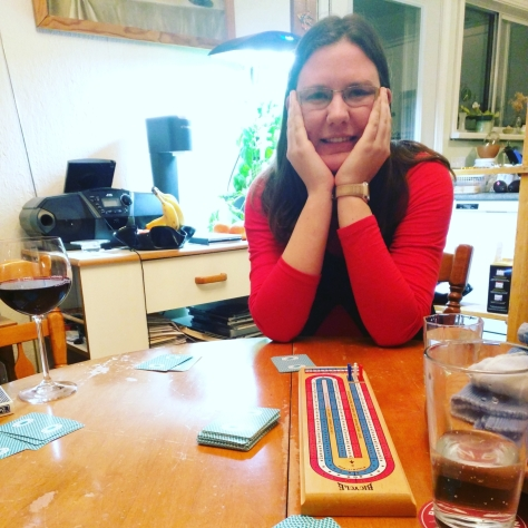 Image description: A young woman in her twenties, with shoulder length brown hair. wearing a red shirt and black jumper smiles at the camera while playing cribbage.