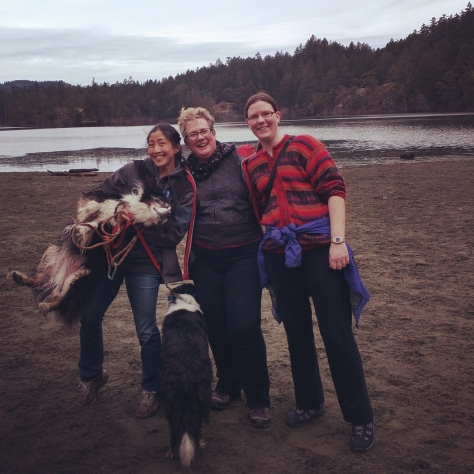 Image description:  There are three women on beach, facing the camera, dressed for col weather hiking.  One of them is holding a dog at waist height. There is a lake and trees in the background.