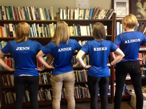 "image description: this colour photo depicts the four women who are on Team Atalanta, from the back, wearing long pants and blue t-shirts with white block letters that state their name. From left to write the shirts say ""JENN,"" ""ANNIE,"" ""KEEKS,"" and ""ALISON."" They are in front of book cases filled with books."
