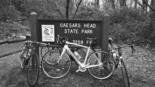 """This image shows my beloved bike, Ruby, against the sign that says """"Caesar's Head State Park, 3208 feet"""""""