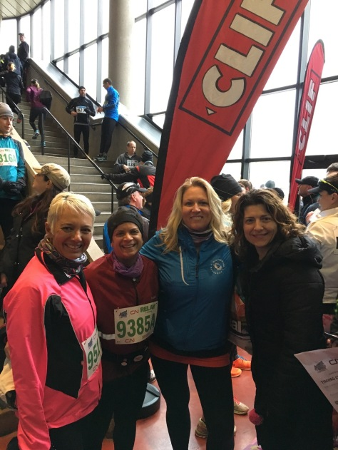 From right to left Tracy (short blond hair) in pink running jacket, Anita (with black ear band) in burgundy running jacket, Julie (with long blond hair, loose) in blue running jacket, and Violetta (with long brown hair, loose) in black winter coat. Everyone is smiling, standing arm in arm in front of a red Clif banner at the bottom of the stairs in First Ontario Centre. Other runners in the background.