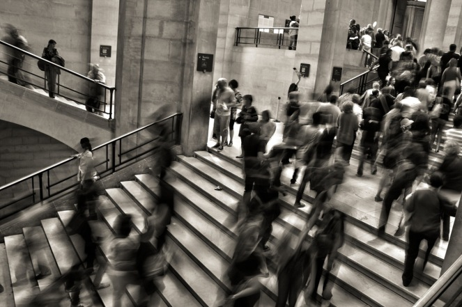 A broad stairwell, like the kind you find at major metropolitan train or subway stations, is filled with people walking up and down the stairs. The people are blurry, imperfectly captured in motion.