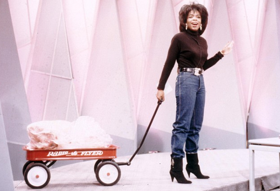 Oprah on her show, with a wagon full of fat, demonstrating her recent weight loss