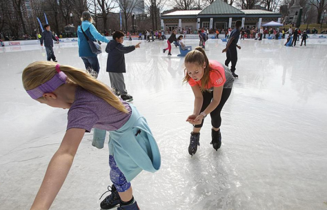 Two girls ice skating on Frog Pond on the Boston common in T shirts and leggings, holding water from the melting ice rink.
