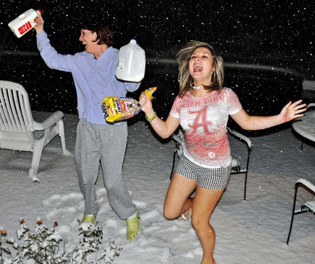 Two women frolicking in the snow holding milk and bread