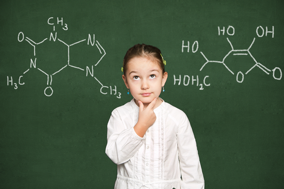 A girl in a white shirt, pondering some molecule diagrams on a blackboard