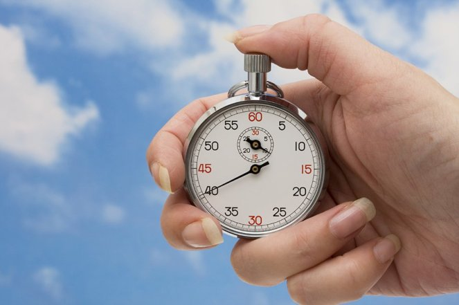 Image description: Stopwatch in a white woman's hand with her thumb on the top button. The silver watch has a white face with black and red numbers and a smaller dial indicating minutes within the larger face indicating seconds. It is in the foreground against a background of blue sky and white wispy clouds.