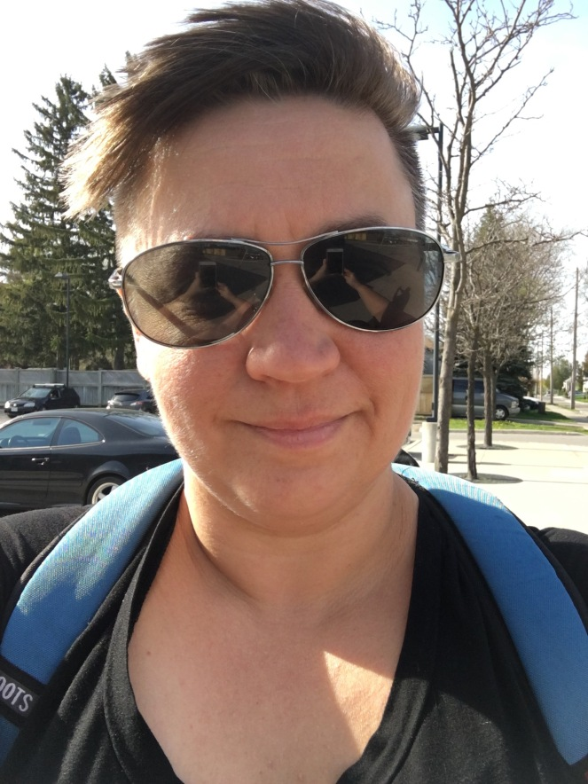A selfie of Natalie wearing sunglasses and a blue backpack. The smile lines on her face frame a slight grin, like she has just let you in on a very funny joke.