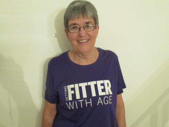 """Image depicts Anne Cummings, a smiling women with short grey hair wearing glasses and a purple t-shirt that says """"GETTING FITTER WITH AGE"""" in white block letters. She is standing against a plain white wall."""