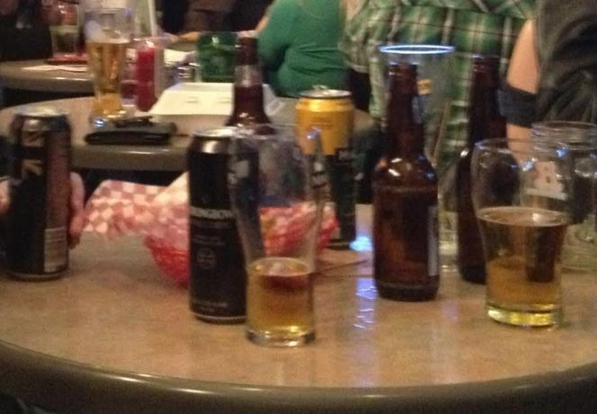 Image description: A table in a bar. On the table there are beer bottles and cans and glasses of beer.