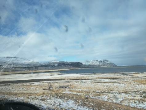 Image description: View from inside the car (brrr!). Blue sky, white clouds, snow covered mountains, and yellow beach in Iceland. On the Snæfellsnes Peninsula.