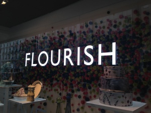 Image shows the word Flourish in capital letters against a dark background of flowers.