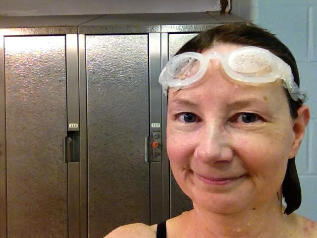 Image description:A headshot of Muriel, a white woman in her early 50s, photographed against a set of silver gym lockers. Muriel is smiling and wearing white swim goggles on her forehead.
