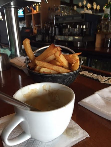 A cappuccino cup and fries on the bar counter