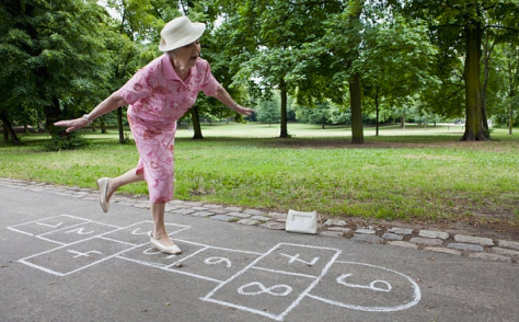 A woman dressed in pink, wearing a white hat, playing hopscotch in a park