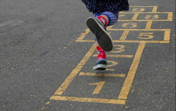 A kid in sneakers and red socks and blue patterned leggings playing hopscotch