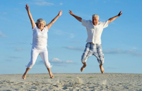 Gray-haired man and woman jumping in the air on a beach with blue sky in the background