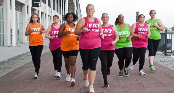 "A group of women of different sizes and colors, all running wearing ""too fat to run?"" tank shirts"