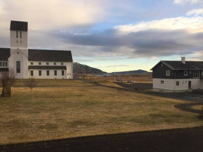 Image description: Sunset at Skálholt. This is the view from our conference bedroom window. The grounds are yellow. The sky is blue. And the clouds are majestic. There are two buildings, on the left a white historic church and on the right a newer conference structure.