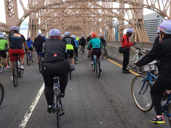That's a rear view of me, riding over the bridge. Black cycling vest, back tights, red Castelli logo.
