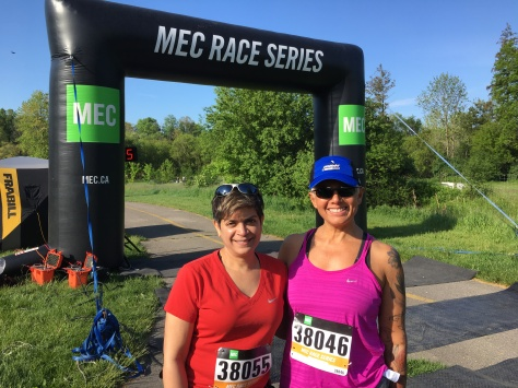 Tracy in dark pink running tank, blue cap, and sunglasses, wearing race bib uber 38046; Anita in short sleeved red v-neck t-shirt, sunglasses atop her head; inflatable MEC Race Series arch in the background.
