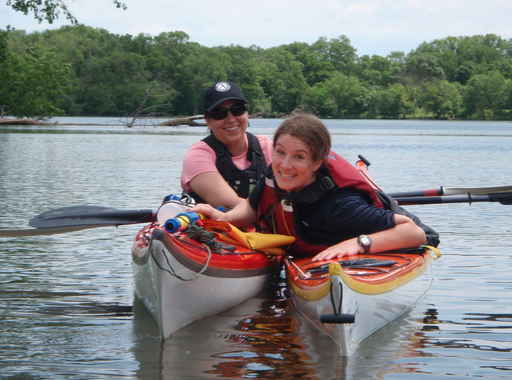 Two smiling women in kayaks, performing an assisted rescue in a lake.