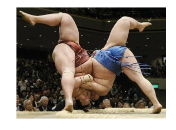 Two sumo wrestlers locked upside down, grappling, with legs in arabesque position.