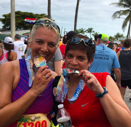 Tracy (left, short blond hair and sunglasses on head, smiling) and Anita (right, short brown hair, sunglasses on head, smiling and holding a water bottle) doing their medal-biting ritual after the Key West Half Marathon in January. Palm trees and people in background; scattered clouds in sky.
