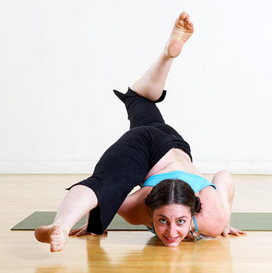 Extreme Acro-yoga pose: woman with chest on floor, left leg up an back, right leg extended to front, arms by side.