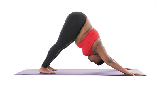 Jessamyn Stanley, yoga teacher and body positivity advocate, in black leggings and orange shirt, facing down on the mat, with arms out in front, legs back on mat, in inverted V.