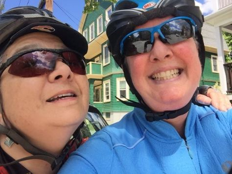 Pata (left) and me, grinning, wearing bike helmets and sun glasses.