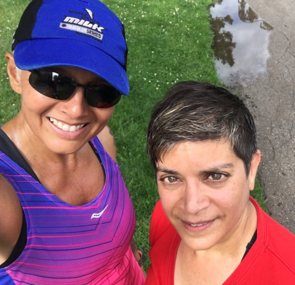 Image description: Selfie of Tracy (left, in blue triathlon cap, sunglasses, and purple and pink running tank) and Anita (right, short brown hair and red t-shirt), with grass, a small puddle with the reflection of a tree, and pavement in the background. Taken at Tracy's 19,000 mark post-long run, pre-breakfast.