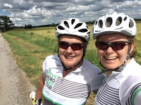 Sam and Sarah, in white jerseys and bike helmets, standing by their bikes. Bright skies but ominous clouds.