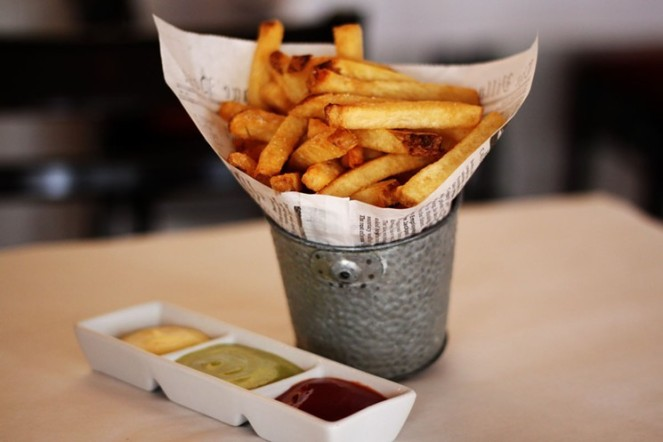 Image description: Steel pail lined with newspaper and filled with a heaping portion of fresh cut fries. Beside it is a three-part condiment dish holding ketchup and two other kinds of dipping sauces for the fries.