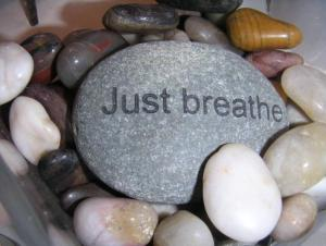 """Image description: a colour image of smooth stones--white, grey, brown, rose-coloured. The largest one in the centre is grey with white specks and has """"Just breathe"""" etched into it."""