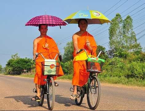 Two monks in orange robes, riding bikes with baskets on the front, also carrying pink plaid and blue/yellow umbrellas for shade on a blue sunny day.