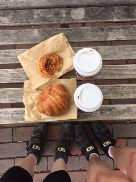 Two cups of coffee, two pastries, two pairs of legs with Sidi bike shoes.