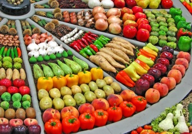 Image description: A coloured picture of an array of raw vegetables arranged in a wedge shaped display that includes peppers, apples, potatoes, peaches, garlic, onions, yams, and brussels sprouts.