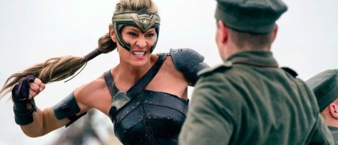 Antiope (portrayed by Robin Wright), dressed in leather battle gear, prepares to punch a WWI German soldier, who is dressed in an olive green military uniform.