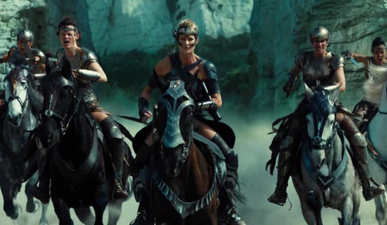 Five women warriors ride horses into battle on a beach. The warriors and horses are wearing metal and leather battle gear. They are led by Antiope, portrayed by Robin Wright.