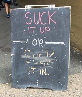 "A sandwich board on the sidewalk: the top part says ""Suck it up"" then an ""OR"", and on the bottom part, someone has partially erased the words ""Suck it in"""