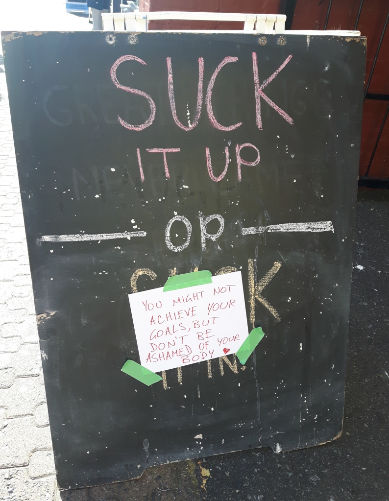 "A sandwich board on the sidewalk. The top part says ""Suck it up"" then an ""Or"" and the bottom part where it says ""Suck it in"" is covered up by a piece of paper taped to the sign saying ""You might not achieve your goals, but don't be ashamed of your body."""