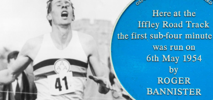 "Image description: Left half is a black and white picture of Roger Bannister, wearing a running tank with two stripes across the chest and the number 41 pinned in front, running through the finish line string, mouth wide open, eyes closed, having just broken the four-minute mile. The right half is blue with white print from a plaque that reads ""Here at the Iffley Road Track the first sub-four minute was run on 6th May 1954 by Roger Bannister."