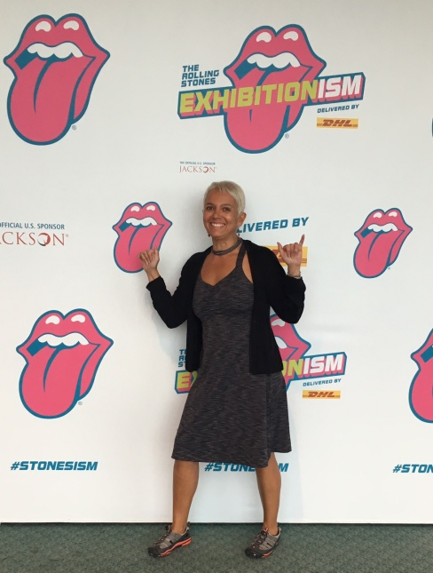 "Image description: Tracy, brown woman with short blond hair, stands smiling and striking a pose in front of a backdrop with the Rolling Stones tongue logo advertising the ""Exhibitionism"" exhibit at Navy Pier in Chicago. She is wearing her grey active dress, grey and orange Keens sandals, a short black cardigan and a grey ribbon choker around her neck."