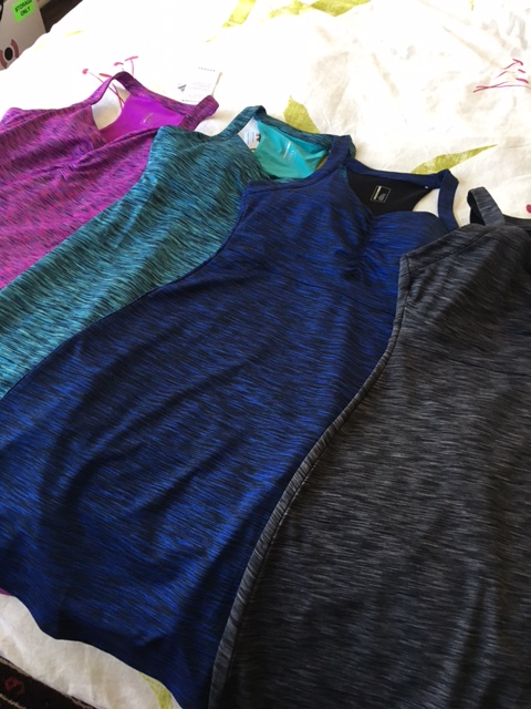 Image description: Tracy's four active dresses laid out on her bed from left to right in purple, turquoise, blue, and grey.