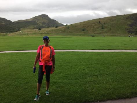Image description: Tracy, in capri running tights, a bright orange running vest over a neon pink running t-shirt, with a neon orange top tied around her waist, a blue cap, white shoes with blue laces and neon yellow trim, smiling. She is standing on grass and a large hill, known as Arthur's Seat, is in the background. Grey cloudy sky above the hill.