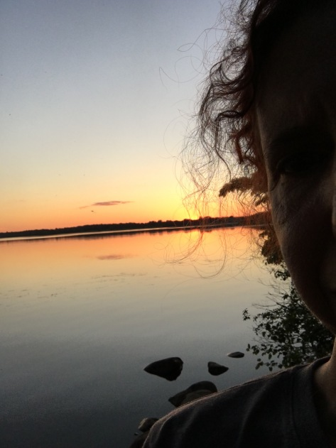 A frame of a woman's face at sunset. In the background is the multicolor sky over a large river.