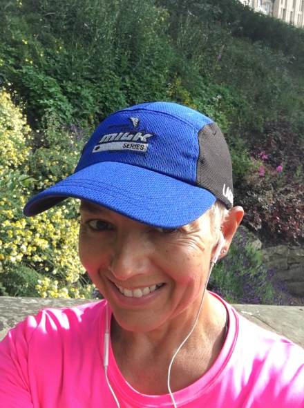 Image description: Tracy in the foreground with a blue running cap, neon pink t-shirt, big smile on her face, and white ear buds. In the background a sloped hill with wild flower garden on it.