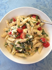 Image: White bowl with pasta noodles, red tomatoes, and green basil.